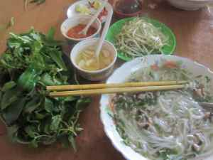 Bowl of pho with side dishes of herbs, chillis, pickled garlic, beansprouts, chilli sauce