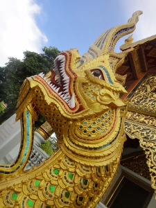 Gilded and glasswork dragon/naga guarding a temple.