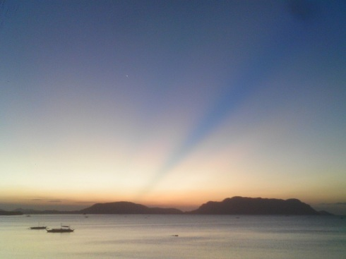 Blue streaks of light in the sky as the sun sets over islands, Tabon, Palawan, Philippines