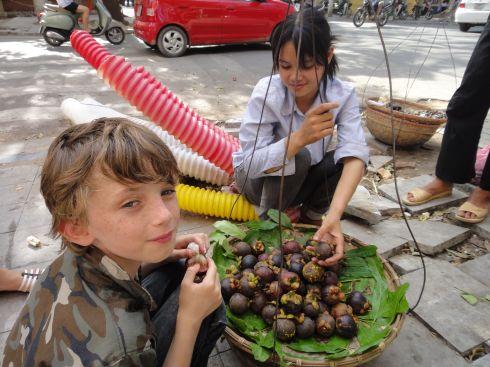 Z enjoying a mangosteen just bought from a street vendor, Hanoi, Vietnam.