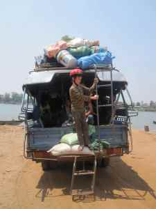 Climbing a ladder on the back of a sangthaew taxi-van. On the Mekong, Four Thousand Islands, Laos.