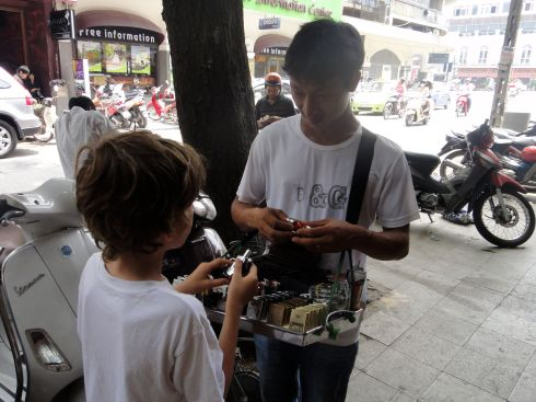 Discussing the finer points of lighters with street vendor, Hanoi, Vietnam.