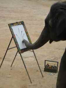 Elephant at an easel, using his trunk to paint. Mae Sa camp, Chiang Mai, Thailand.