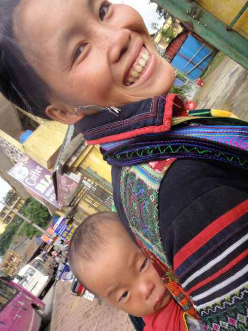 Hmong hilltribe mother with baby on back, Sapa, Vietnam.