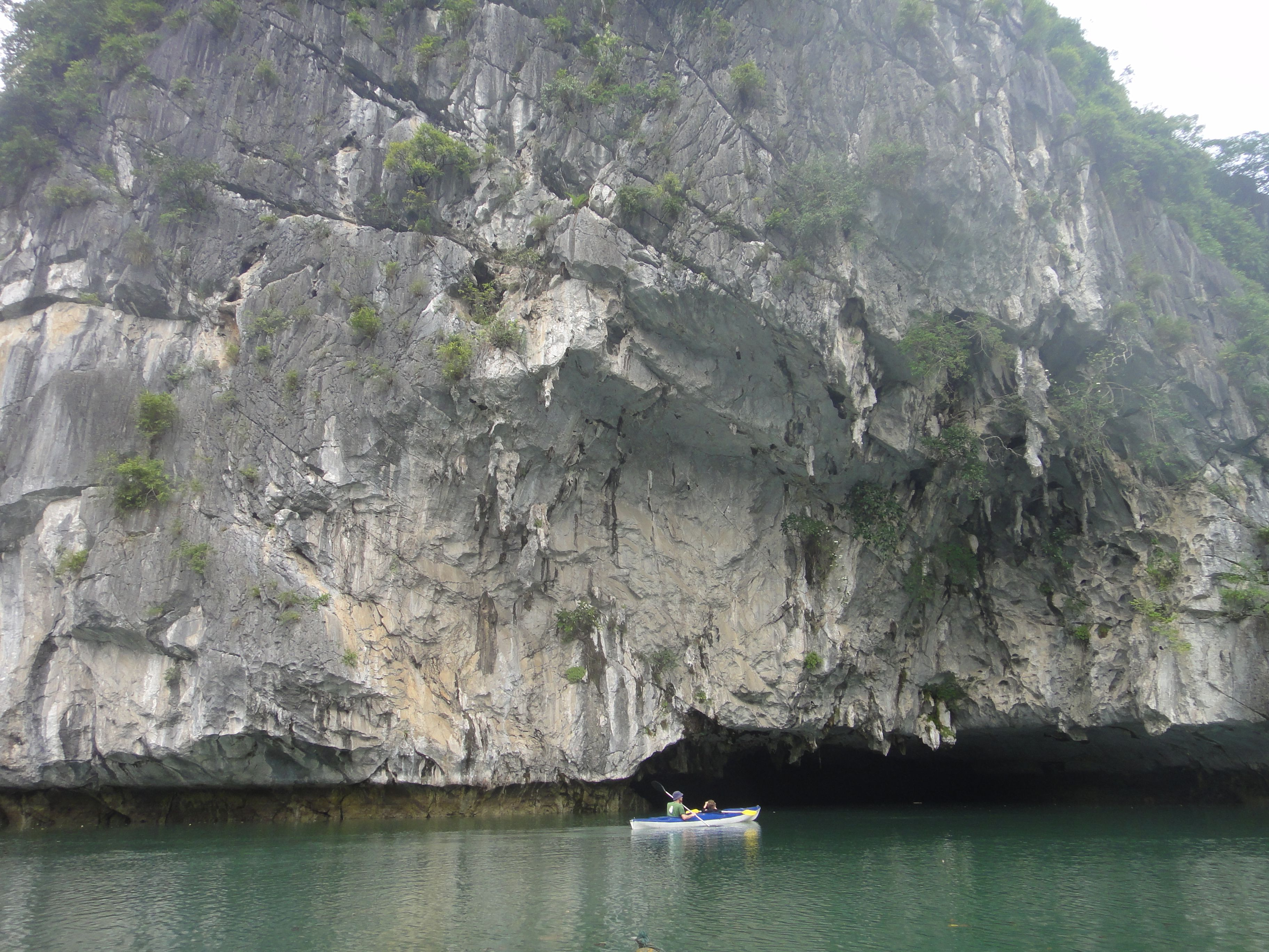 Kayaking into cave archway in base of cliffs, Halong Bay, Vietnam.