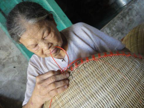 Elderly lady sewing the rim of a basket, Vietnam.