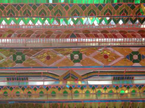 Repeating patterns of mirrored mosaics, altar of side temple, Wat Chiang Man, Chiang Mai, Thailand.