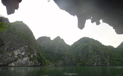 Stalactites dangle from the mouth of a cave, giving onto a marine lake, halong Bay, Vietnam.