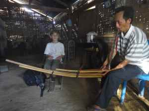 Hmong man in his house playing the qeej, while Z looks on.