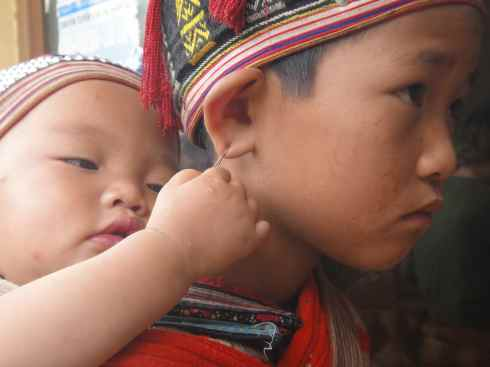 Baby brother playing with his sister's earring: Sapa, Vietnam.
