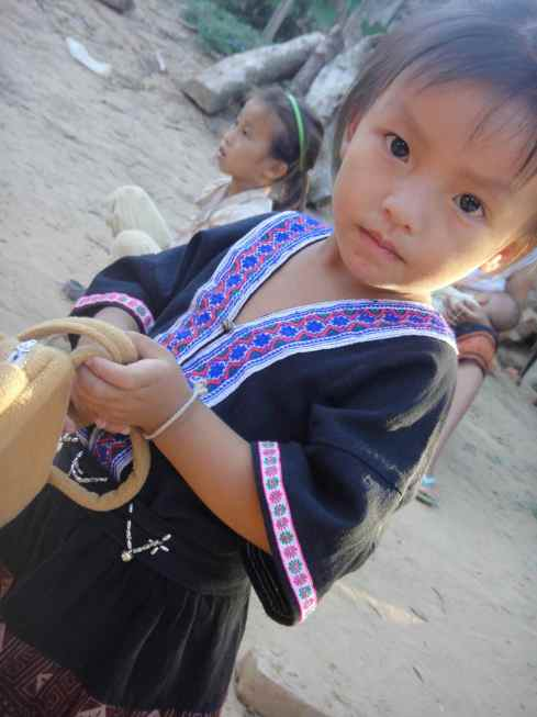 Four year old Hmong girl holds a handbag, Luang Namtha province, Northern Laos.