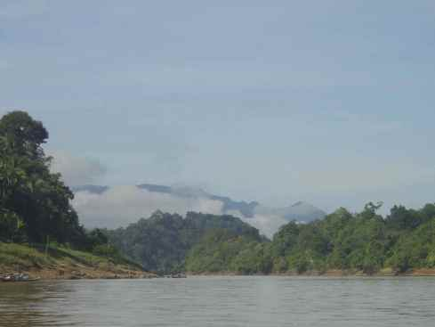 view up the Balui River, Sarawak, Borneo, Malaysia, with clouded hills, smooth water and forest descending to the river.