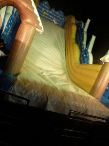 illuminated inflatable slide at funfair in Sarawak, with safety rail but no landing mat.