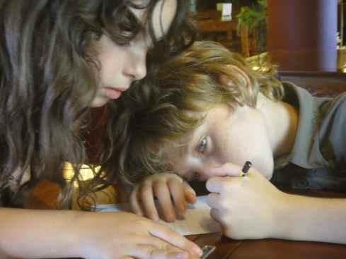 Closeup of Z and Solene drawing at a table.