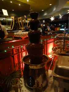chocolate fountain: three-tier container with molten chocolate pouring over it.