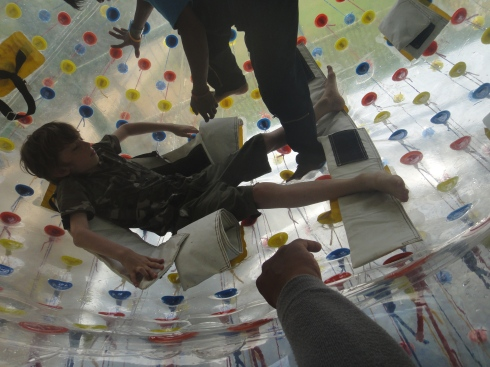 Inside the inflatable ball, Z is strapped inside by helpers.