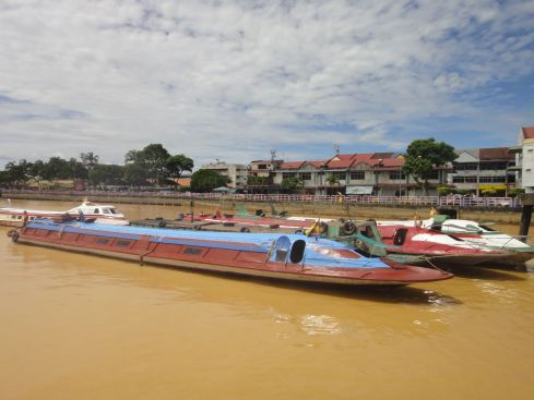 Long, low, closed steel express boats waiting in port on the golden waters of the Batang Rejang, Sarawak, Borneo, Malaysia.
