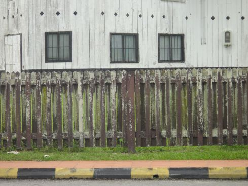 Section of Fort Sylvia, in Kapit, white-washed timber, wooden fence, pavement and road. Sarawak, Borneo, Malaysia.