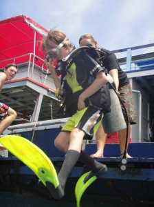 Z in scuba gear exiting a boat with a giant stride.