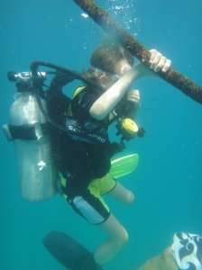 Z descending a guideline under the water in scuba gear, one hand on the rope.