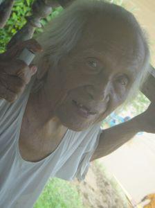 Hundred year old Kayan man watching teams training for the Sarawak regatta. Balui River, Sarawak, Malaysia, Borneo.