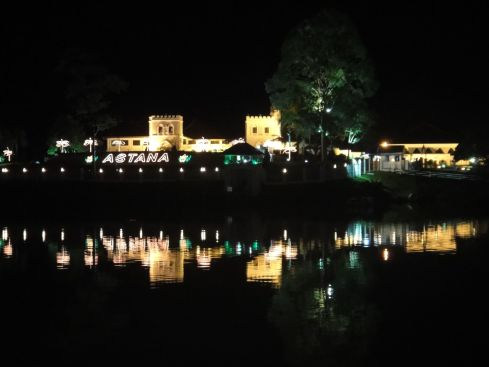 Astana, the fortress-like state residence of the Governor of Sarawak, illuminated at night, reflecting in the Sarawak River. Kuching, Sarawak, Borneo, Malaysia.