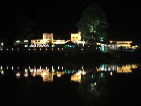 Astana, the fortress-like state residence of the Governor of Sarawak, illuminated at night, reflecting in the Sarawak River. Kuching, Sarawak, Borneo, Malaysia.