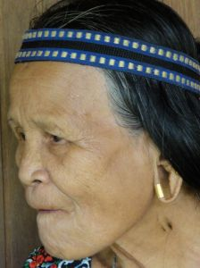 Old Lanahan lady chewing betel between toothless gums, with headband and an earring worn around the outside of the gaping hole in her earlobe. Balui River, Borneo, Sarawak, Malaysia.