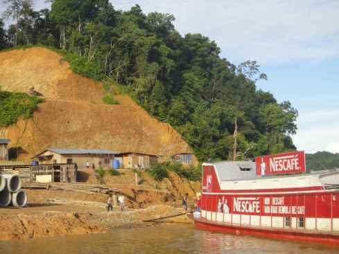 Logging camp set against a scarred hillside on the banks of the Batang Rejang, with Nescafe branded delivery boat in the foreground.