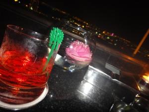 Negroni cocktail and floating rose over Bangkok skyline, Vertigo