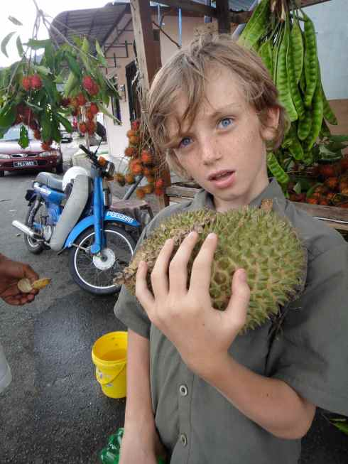 Z holding small durian with expression of horror. Teluk Bayang, Malaysia.