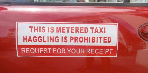 "Sign on Malaysian taxi door, reading ""This is metered taxi. Haggling is prohibited. Request for your receipt."""