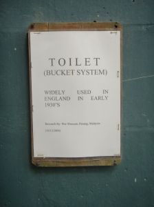 """Sign on wall reading: """"Toilet (Bucket system). Widely used in England in the 1930s."""""""