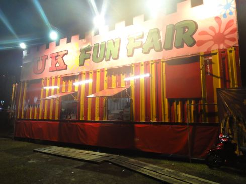 Illuminated fairground entrance with the legend UK Funfair, Bintulu, Sarawak, Borneo, Malaysia.