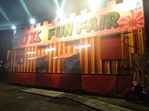 Illuminated fairground entrance with the legend UK Funfair, Bintulu, Sarawak, Borneo, Malaysia.