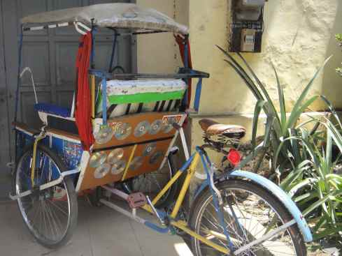 Becak customised with CDs against pale yellow wall with tropical plants. Makassar, Indonesia.