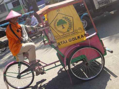 Becak driver on pink and gold rickshaw. Makassar, Indonesia.