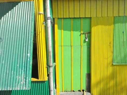 Yellow and green corrugated iron restaurant shack, Makassar port, Indonesia.