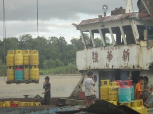 Canisters of cooking gas being loaded onto a boat. Secured with plastic packing tape. Marudi, Sarawak, Borneo, Malaysia.