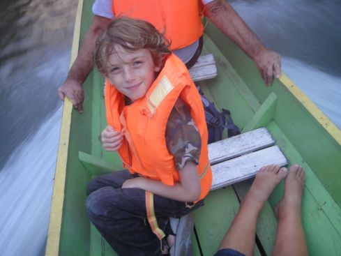 Z in orange lifejacket in longboat en route to Mulu National Park with his grandparents.
