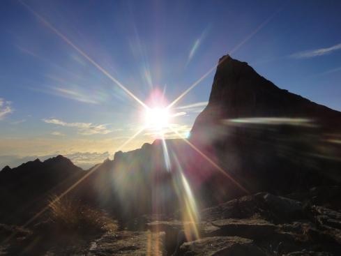 sun bursts above peaks on the summit of mount kinabalu, borneo, malaysia