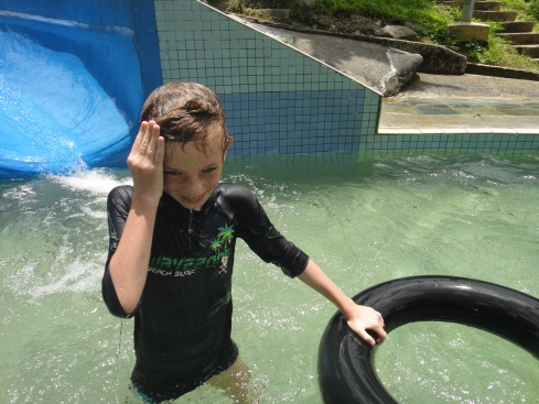 Z, grinning, coming off slide with rubber ring. Poring Hot Springs, Kinabalu Park, Sabah, Borneo, Malaysia.
