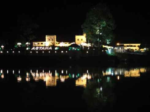 James Brooke's palace, the Astana, illuminated at night and reflected in the river. Kuching, Sarawak, Borneo, Malaysia.
