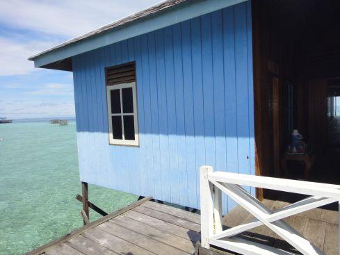 Room on stilt pier over jade green sea. Losmen Danakan, Pulau Derawan, Indonesia.