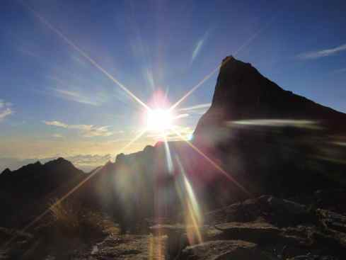 Sunrise on the summit of Mount Kinabalu, bursting from behind a peak in shining rays. Sabah, Borneo, Malaysia.