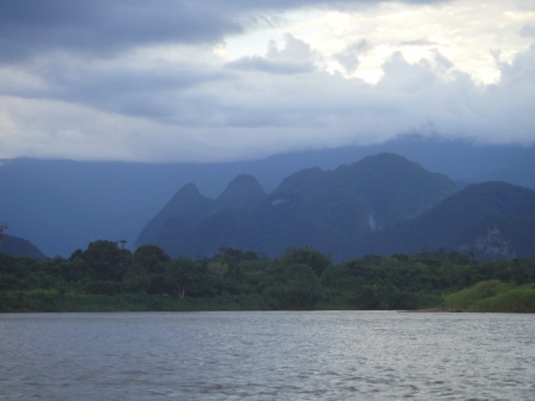 The river gives on to jungle and stark hills set against the larger mountain range. Mulu National Park, Sarawak, Borneo.