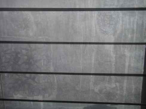Textured grey plaster seen through the slats of a window. Makassar, Indonesia.