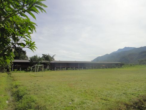 Modern wooden longhouse on grassy expanse with mountains in the background. Long Iman, Mulu, Sarawak, Borneo.