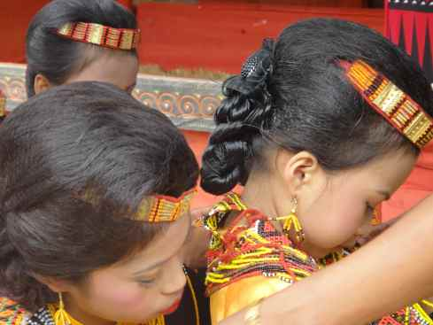 Older relative adjusts young mourner's bead waistlet: Torajan funeral, Tana Toraja, Sulawesi, Indonesia.