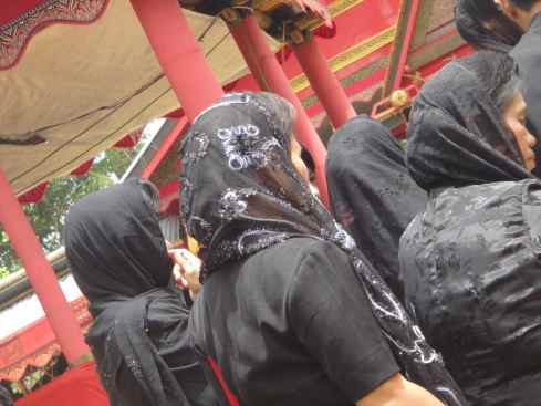 Women dressed in black with black mantillas process to reception at Torajan funeral: Tana Toraja, Sulawesi, Indonesia.